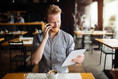 Busy blogger multitasking. Busy handsome smart blogger multitasking in cafe stock photos