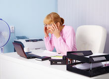 Busy blonde in office workplace Royalty Free Stock Photography