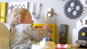 Busy-board for children. Cute baby boy playing with busy board on the wall stock video