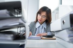 Busy bookkeeper. Pretty busy bookkeeper between folder stacks stock photography