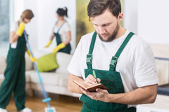 Busy boss and his cleaning company. Busy young boss of cleaning company writing down the notes Stock Photography