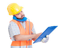Busy builder using phone while holding clipboard Royalty Free Stock Photography