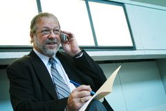 Busy business man. Middle age business man talking with his cell phone Royalty Free Stock Images