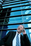 Busy business man. Business man in a hurry talking on cell phone.  Blue modern building behind him Royalty Free Stock Photos
