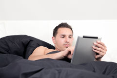 Busy Business man. An attractive young business man is working in there bed Stock Photography