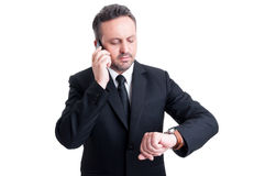 Busy business man checking watch. Busy business man checking the watch while talking on the phone Royalty Free Stock Photo