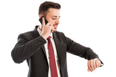 Busy business man concept. Showing an entrepreneur talking on the phone while checking the watch Royalty Free Stock Photo