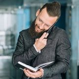 Busy business man check day planner talk phone. Busy business man lifestyle. guy checking with his day planner and talking on the phone royalty free stock photo