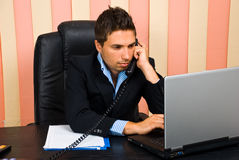 Busy business man in office. Sitting on chair at desktop talking by telephone and typing on laptop,check also Business people Royalty Free Stock Images