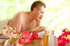 Busy business man in spa salon. Even in spa business man is busy working using his laptop and phone Royalty Free Stock Image