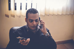 Busy business man. Talking on mobile and holding another one Royalty Free Stock Photography