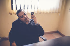 Busy business man. Talking on mobile with holding another one Royalty Free Stock Images
