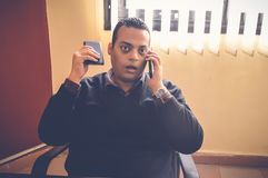 Busy business man talking on mobile. While holding another one Royalty Free Stock Image