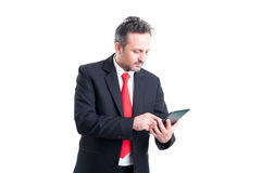 Busy business man using wireless tablet. Busy business man holding and using wireless tablet Stock Images