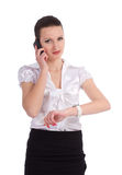 Busy business woman checking time while talking on. Cellphone over white background Royalty Free Stock Photography