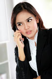 Busy business woman using a mobile phone Royalty Free Stock Image