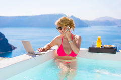 Busy business woman working while on vacation in pool Stock Image
