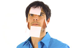 Busy Businessman. Overworked and tired businessman with yellow sticky reminder notes isolated over white Stock Photography
