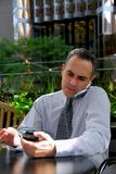 Busy businessman. Portrait of a busy businessman in the city using pda and cell phone Royalty Free Stock Photo