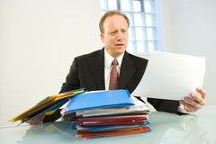 Busy businessman. A middle aged businessman overloaded with work files on his office desk Royalty Free Stock Photos