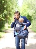 Busy businessman with his son in a sling talks on the smartphone. And try to opens up a backpack with documents, front view Stock Photography