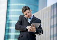 Busy businessman holding digital tablet and mobile phone overworked outdoors Stock Images