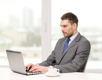 Busy businessman with laptop and coffee Royalty Free Stock Images