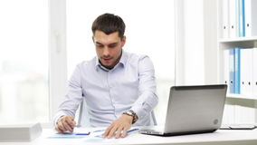 Busy businessman with laptop and papers in office stock video
