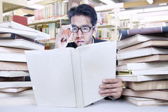 Busy businessman at library. Young businessman is busy reading a book at the library royalty free stock image