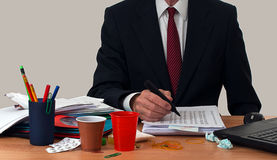 Busy businessman or office worker, at untidy desk. With coffee cups, aspirins and lots of work Royalty Free Stock Images