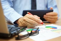 Busy businessman overwhelmed with informations  on tablet comput. Er, laptop and documentation Royalty Free Stock Photo
