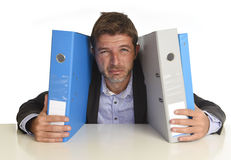 Busy businessman overwhelmed in stress at office exhausted holding paperwork folders Royalty Free Stock Image