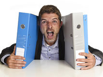 Busy businessman overwhelmed in stress at office exhausted holding paperwork folders Stock Photography