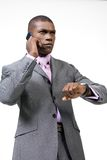 Busy Businessman on Phone. Young, black businessman with serious look on face, talking on cellphone while checking his watch Royalty Free Stock Photo