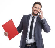 Busy businessman with phone and folders Royalty Free Stock Image