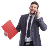 Busy businessman with phone and folders Stock Photography