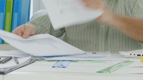 Busy businessman select and arrange papers plans graph and charts.  stock footage