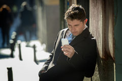 Busy businessman in suit and tie using mobile phone sending message or consulting internet Royalty Free Stock Image