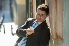Busy businessman in suit and tie using mobile phone sending message or consulting internet Stock Photos