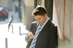 Busy businessman in suit and tie using mobile phone sending message consulting internet Royalty Free Stock Photo