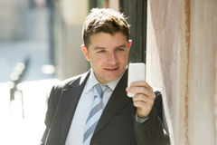 Busy businessman in suit and tie using mobile phone sending message or consulting internet Stock Images