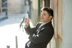 Busy businessman in suit and tie using mobile phone sending message or consulting internet Royalty Free Stock Photos