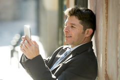 Busy businessman in suit and tie using mobile phone sending message or consulting internet Royalty Free Stock Images
