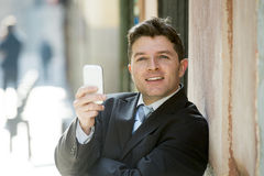 Busy businessman in suit and tie using mobile phone sending message or consulting internet Stock Photo