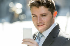 Busy businessman in suit and tie using mobile phone sending message or consulting internet Royalty Free Stock Photography