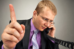 Busy businessman talking by phone Stock Photo