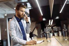 Busy businessman talking on phone Stock Images