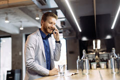 Busy businessman talking on phone Royalty Free Stock Image