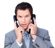 Busy businessman using two telephones Stock Image