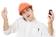 Busy businessman wearing a helmet with a phones Royalty Free Stock Images